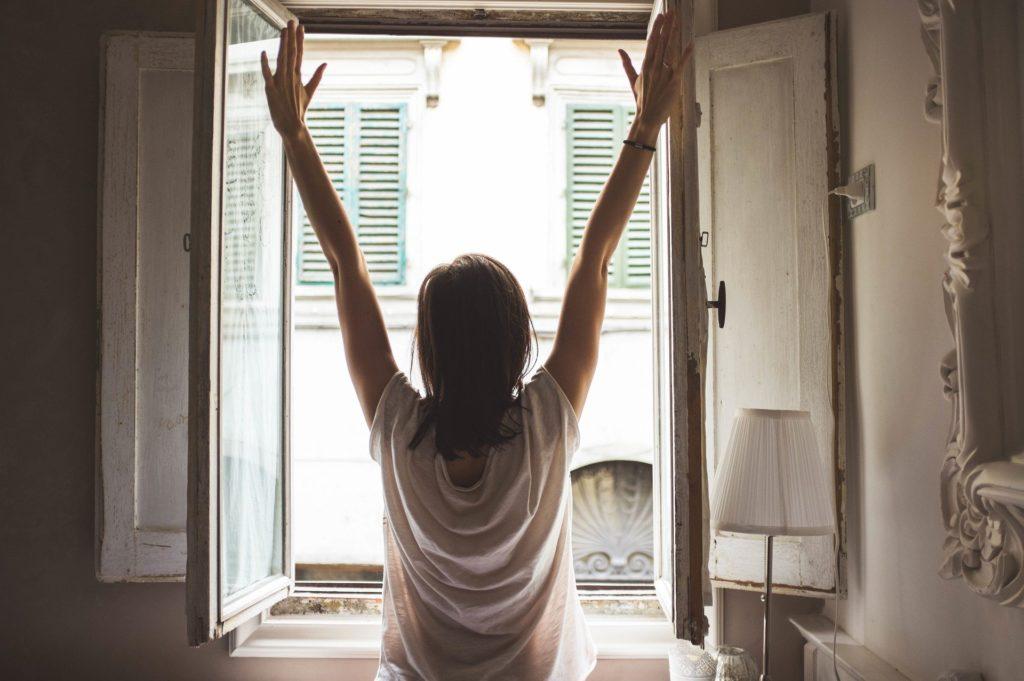 femme devant une fenetre en vitrage simple ouverte